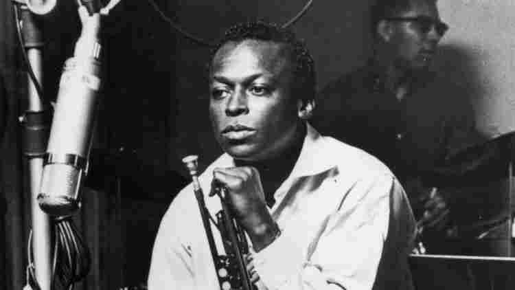 American jazz trumpeter and composer Miles Davis sits with his horn during a studio recording session, October 1959.