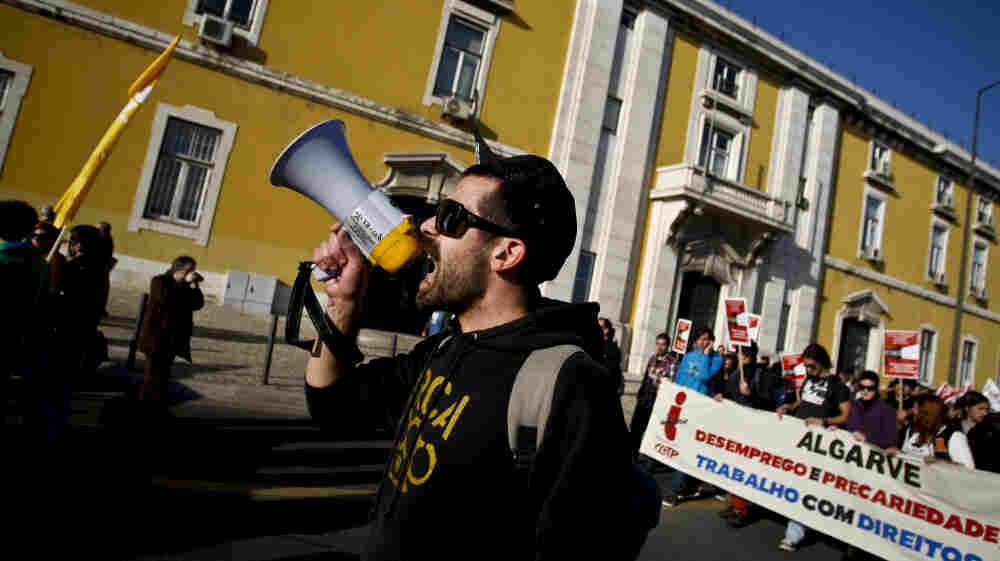 Protesters against government austerity measures march in front of the Finance Ministry in Lisbon, Portugal, earlier this month. The country's debt crisis has prompted Portuguese workers to look to their country's former colonies for jobs.