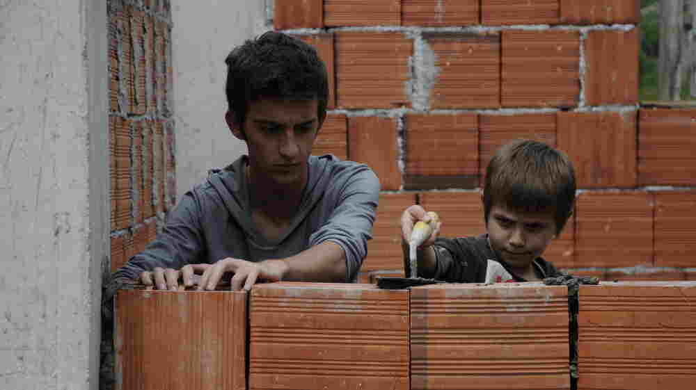Nik (Tristan Halilaj, left) and his younger brother, Dren (Elsajed Tallalli), must both stay indoors to avoid violent retaliation after their father kills a member of another family.