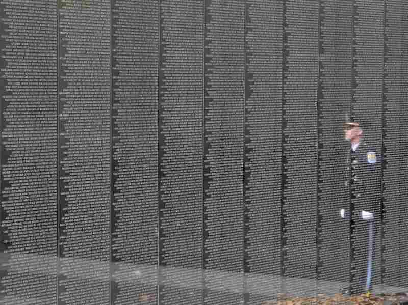 An officer is reflected on the Vietnam Veterans Memorial during a ceremony for Veterans Day in 2011.