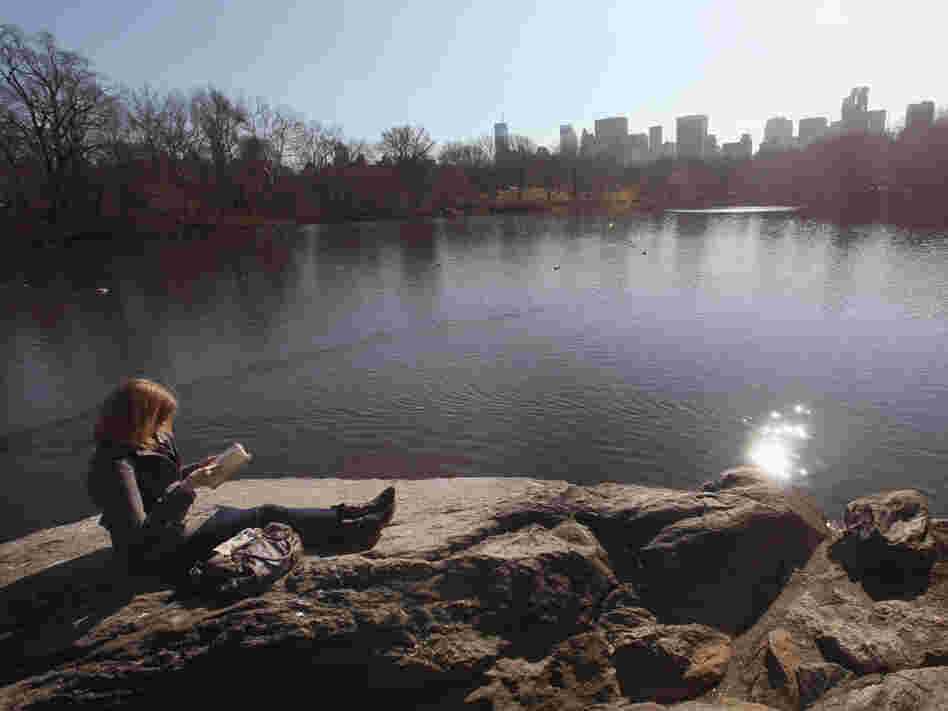 A woman takes in the sunshine while reading in Central Park on Feb. 1 in New York City, where temperatures topped 60 degrees.