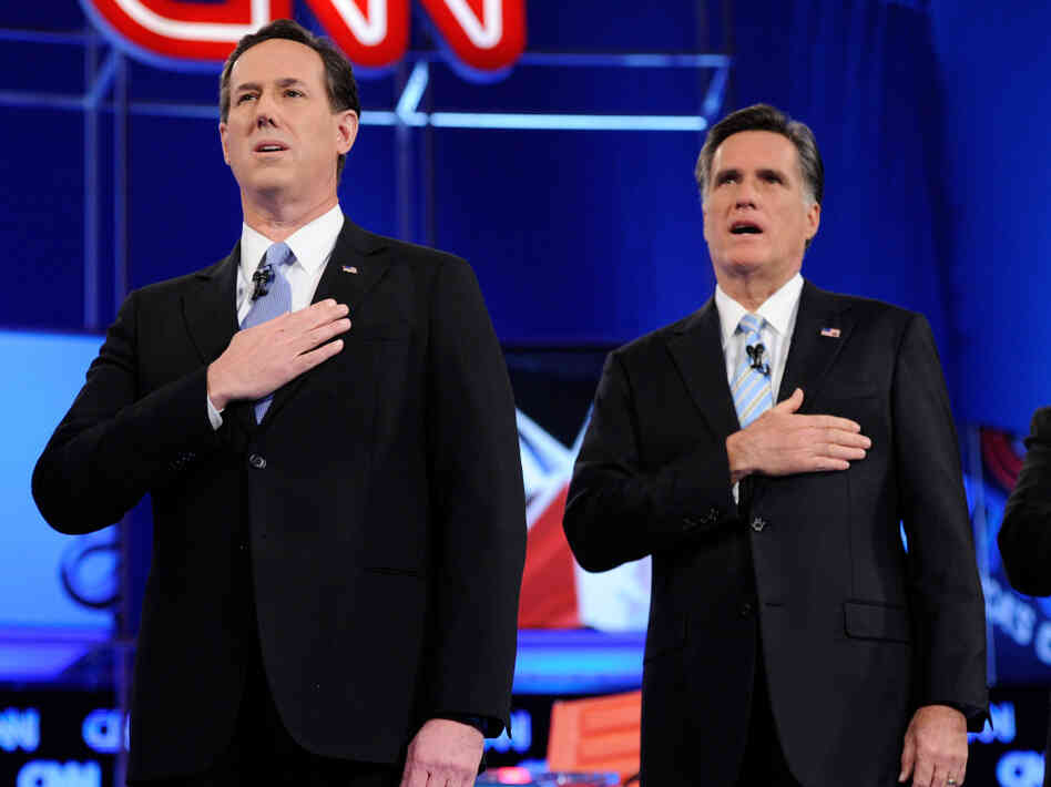 Republican presidential candidates Rick Santorum and  Mitt Romney sing the national anthem at a debate Feb. 22, 2012 in Mesa, Arizona. The debate was the last one scheduled before voters head to the polls in Michigan and Arizona's primaries on Feb. 28 and Super Tuesday on March 6.