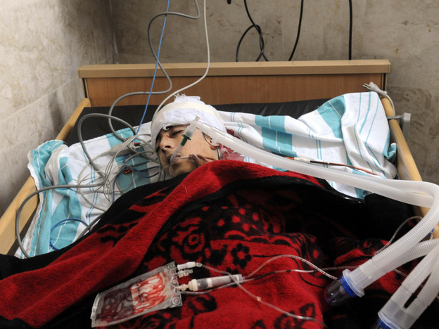 Zouheir Jabbour says many of the videos and images coming out of Syria are a fabrication. Here, a badly injured man lies in a bed at a makeshift clinic in the Syrian city of Idlib on Friday.