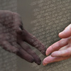 A visitor touches names engraved on a traveling half-scale replica of the Vietnam Veterans Memorial in Washington, D.C.