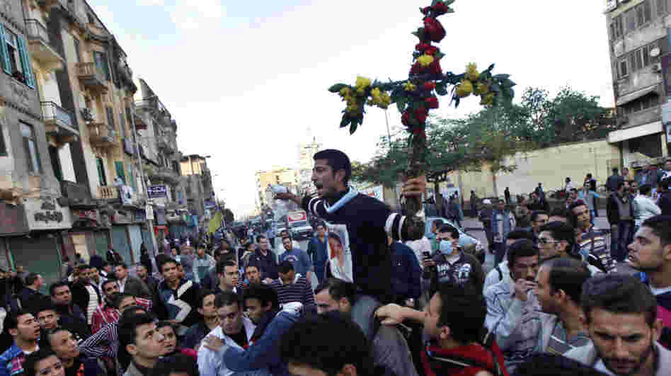 A Coptic Christian man holds a cross made of flowers during a clash between Christians and Muslims in Cairo in November. Relations are becoming more strained between the two communities, and there has been periodic violence.