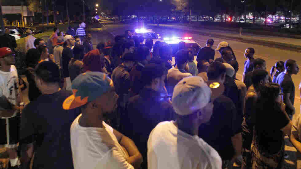 Police hold back crowds near The Florida Mall in Orlando, Fla. late Thursday.