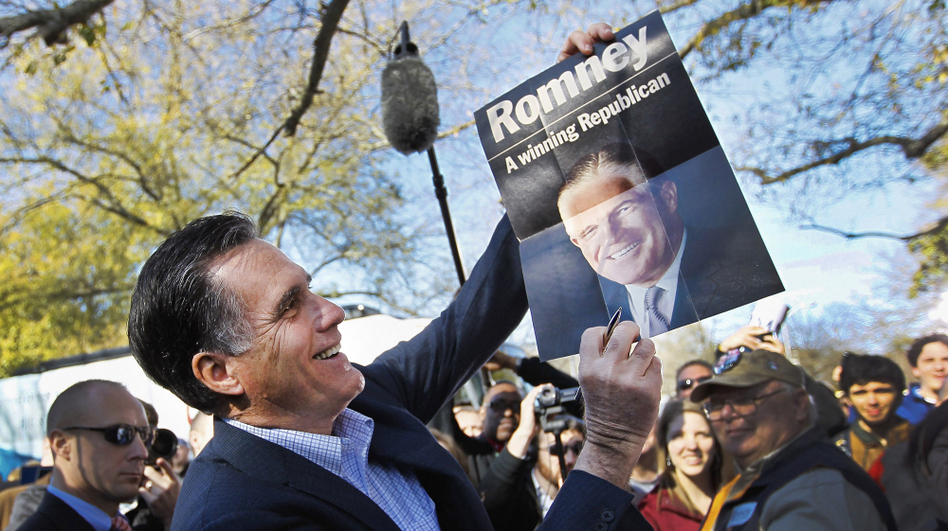 Republican presidential candidate Mitt Romney holds up a poster of his father, George Romney, who was the former governor of Michigan, after it was given to him while greeting people at a campaign rally at Wofford College on January 18 in Spartanburg, South Carolina.
