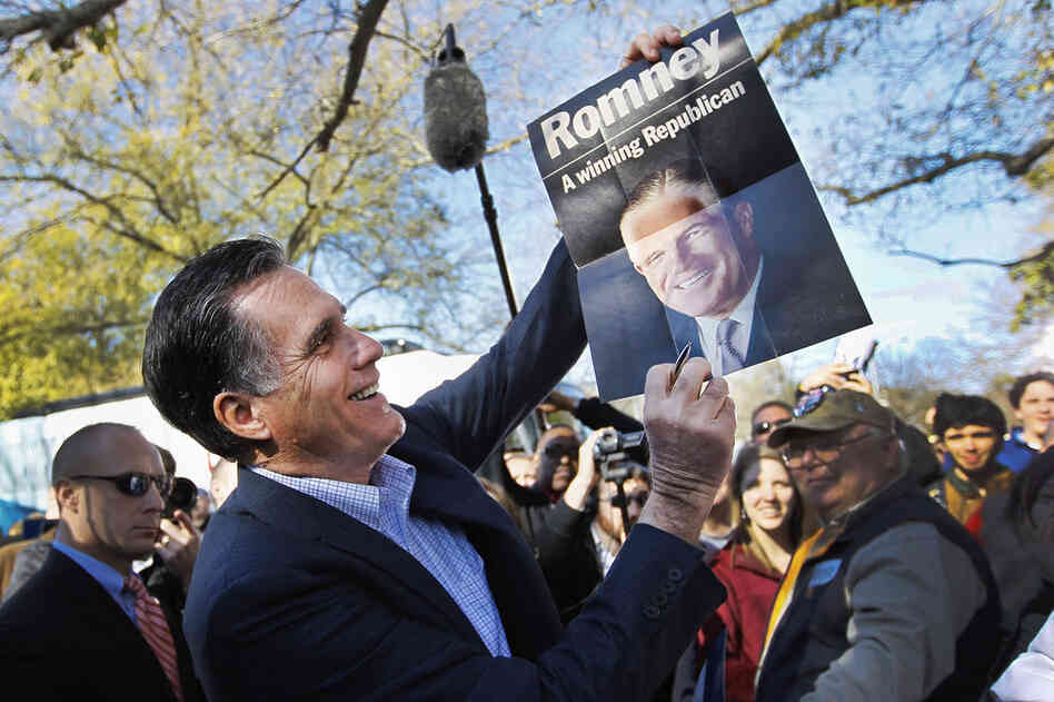Mitt Romney holds a poster of his father, given to him at a campaign rally in Spartanburg, S.C., in January.