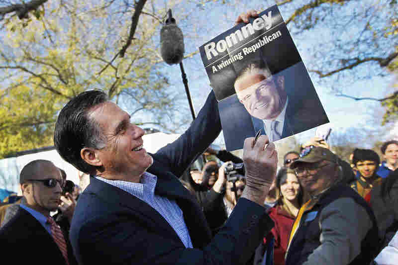 Mitt Romney holds a poster of his father, given to him at a campaign rally in Spartanburg,