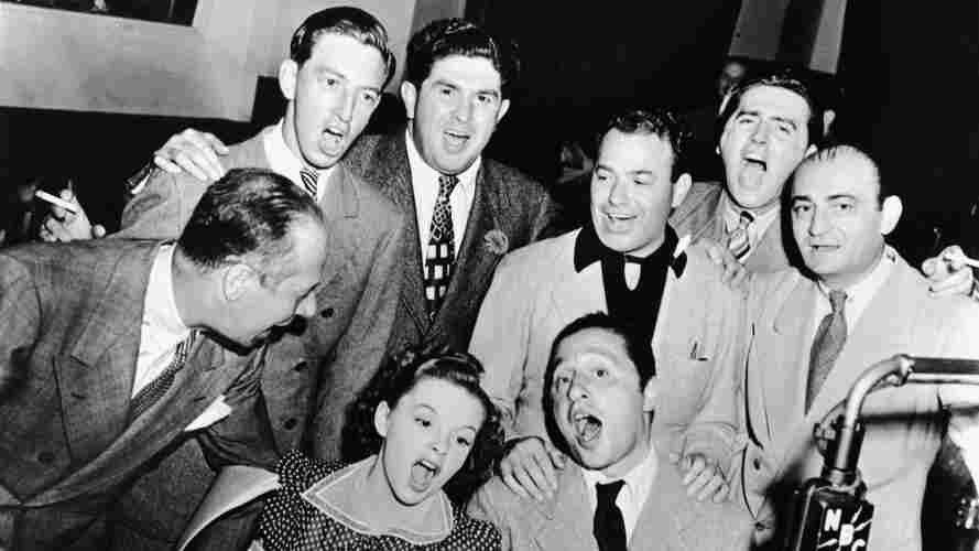 Bert Lahr (far right), Ray Bolger (back row, right), Judy Garland (sitting, right), composer Harold Arlen (sitting left), and various MGM and music publishing executives sing songs from the 1939 film musical 'The Wizard of Oz' around a microphone in the NBC radio studio, circa 1939.