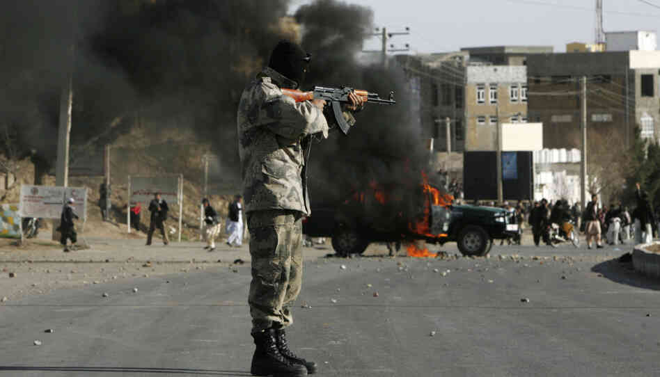 An Afghan policeman aims at protesters by a burning police truck set alight during an anti-U.S. demonstration on Friday over burning of Qurans at a U.S. military base