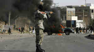 An Afghan policeman aims at protesters by a burning police truck set alight during an anti-U.S. demonstration on Friday over burning of Qurans at a U.S. military base in Afghanistan.