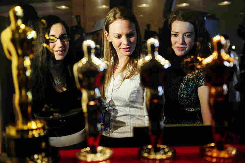 """Oscar fans in New York take a closer look at the statuettes on display during the """"Meet the Oscars, Grand Central"""" exhibition at Grand Central Station on Feb. 22."""