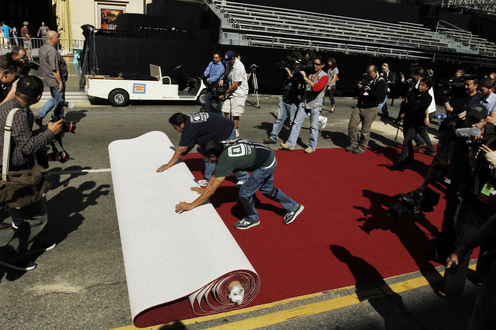 Workers roll out the red carpet as press photographers clamor to capture the moment as Oscar night approaches.