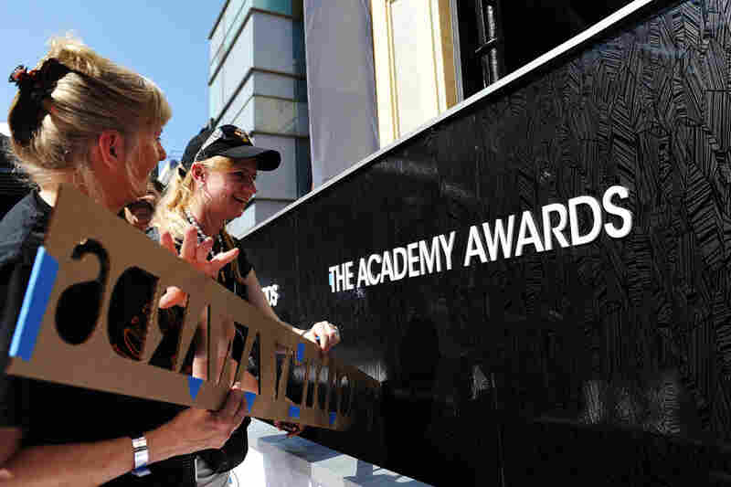 Crew members apply a fixture onto a wall of the red carpet for this year's Academy Awards hosted by Billy Crystal.