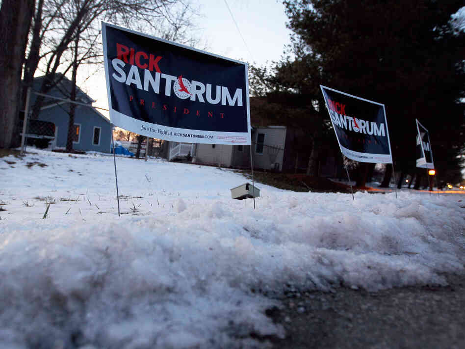 Polls show Rick Santorum and Mitt Romney in a tight race heading into Tuesday's Michigan primary. Santorum's campaign signs are stuck in the snow before his campaign stop at the The Colonial Valley Suites on Feb. 26 in Davison, Mich.