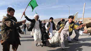 The latest violence in Afghan has raised doubts about the U.S. strategy. Here, Afghan demonstrators shout anti-U.S. slogans as they carry a wounded man during a protest in the Western city of Herat on Feb. 24.