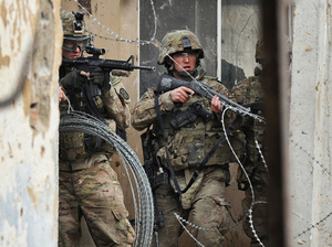 Two U.S. troops guard the gate at the Bagram Air Field north of Afghanistan's capital, Kabul, on Feb. 21. U.S. officials say troops inadvertently burned Qurans at the base, which has touched off violent protests around the country.