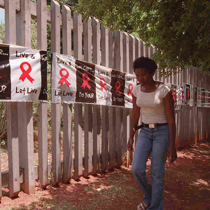 A woman walks past a banner placed around the perimeter of the Rand Afrikaans University in Johannesburg on World AIDS Day. The university used the banner to raise public awareness about AIDS and the devastating toll the disease has had in South Africa.