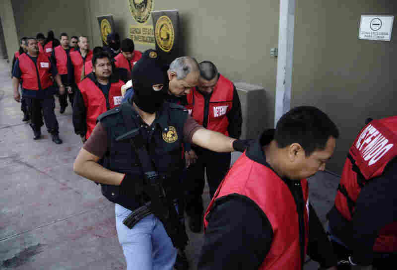 The warden and guards of the Apodaca prison are escorted away after a press conference in Monterrey, Mexico, Feb. 22. The director, deputy director and the chief of security along with 26 guards are under arrest for allegedly assisting members of the Zetas drug cartel orchestrate an escape and the killing of members of the rival Gulf cartel.