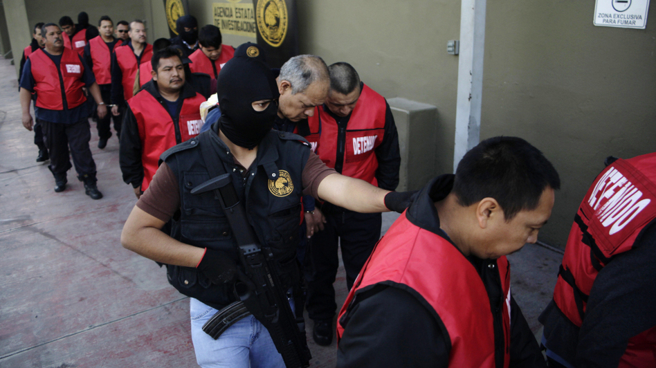 The warden and guards of the Apodaca prison are escorted away after a press conference in Monterrey, Mexico, Feb. 22. The director, deputy director and the chief of security along with 26 guards are under arrest for allegedly assisting members of the Zetas drug cartel orchestrate an escape and the killing of members of the rival Gulf cartel. (Reuters/Landov)