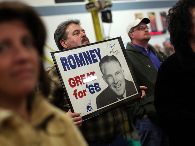 A supporter of Republican presidential candidate Mitt Romney holds a vintage campaign poster of Romney's father, George Romney, in Albion, Mich.
