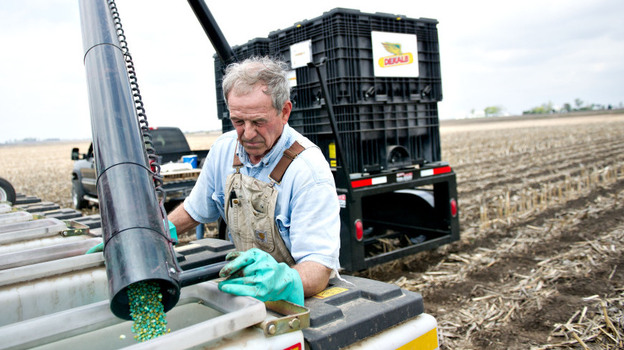 Farmer Alan Madison fills a seed hopper with Monsanto hybrid seed corn near Arlington, Illinois, U.S. A group of organic and other growers say they're concerned they'll be sued by Monsanto if pollen from seeds like these drift onto their fields.  (Landov)