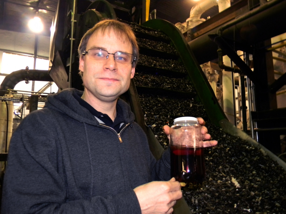 JBI CEO John Bordynuik holds a jar of No. 6 fuel oil, derived from discarded plastic like that seen on a conveyor belt at his plant.