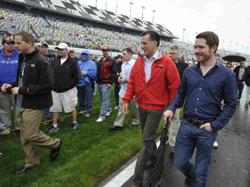 Mitt Romney walks with driver Brian Vickers at the Daytona International Speedway in Florida on Sunday, Feb. 26, 2012.