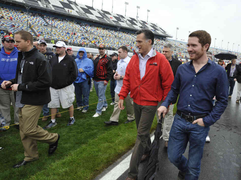 Mitt Romney walks with driver Brian Vickers at the Daytona International Speedway in Florida on Sunday, Feb. 26, 2012.