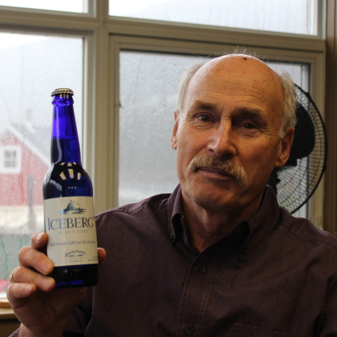 Charlie Rees, who gives tours of Quidi Vidi Brewing Co., holds a bottle of Iceberg beer.