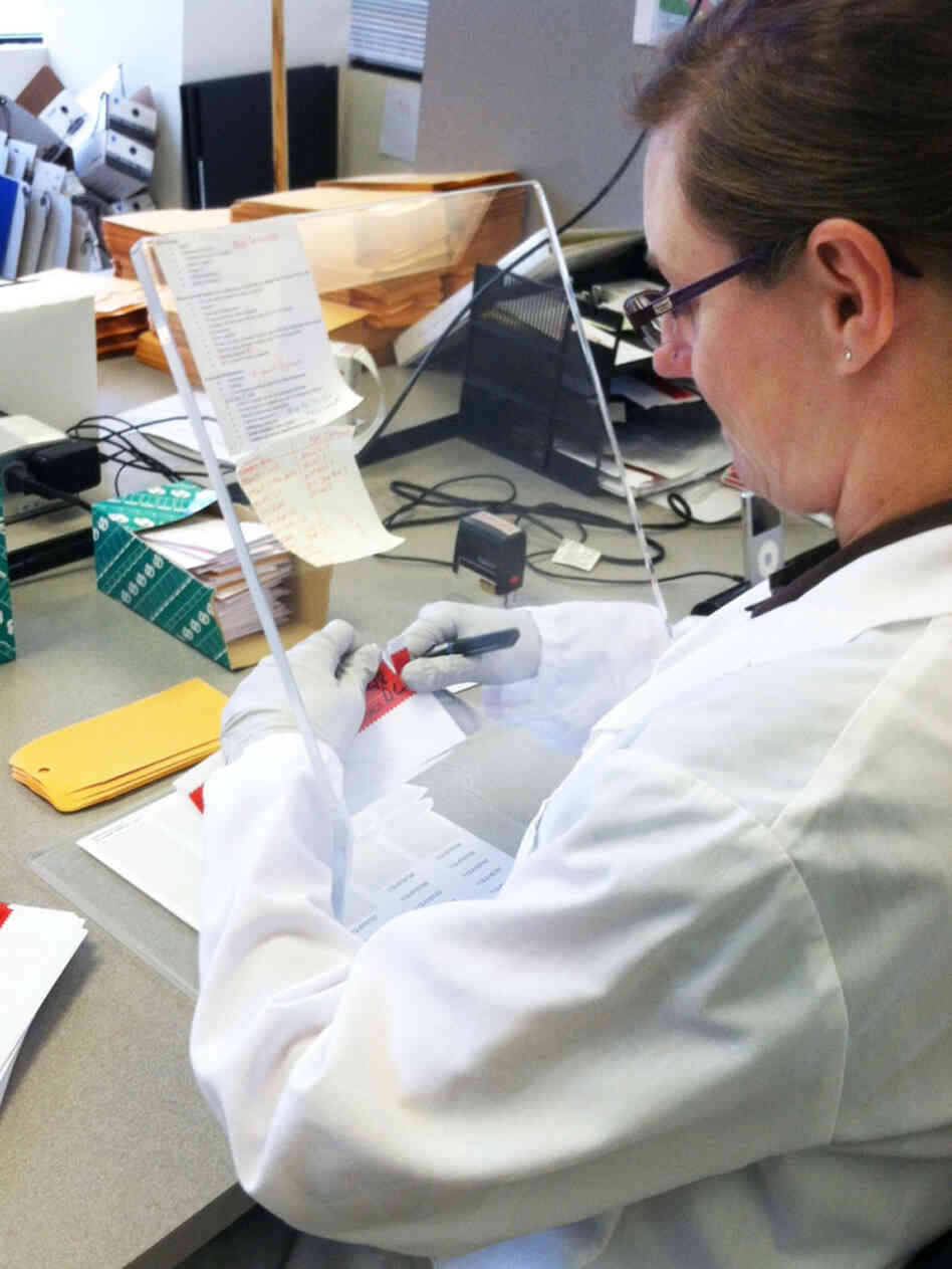 A Washington State Patrol crime lab technician opens DNA sample cards containing cheek swabs sent from jails and prisons. If the state Legislature approves pre-