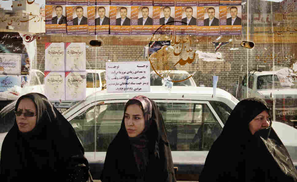 Women sit at a bus stop under election posters in Qom, about 75 miles south of Iran's capital, Tehran, on Tuesday. Iran's parliamentary elections on Friday are expected to be a contest between various conservative factions. Many candidates seeking change have been barred from running.