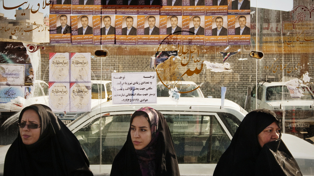 Women sit at a bus stop under election posters in Qom, about 75 miles south of Iran's capital, Tehran, on Tuesday. Iran's parliamentary elections on Friday are expected to be a contest between various conservative factions. Many candidates seeking change have been barred from running.  (Reiters/Landov)