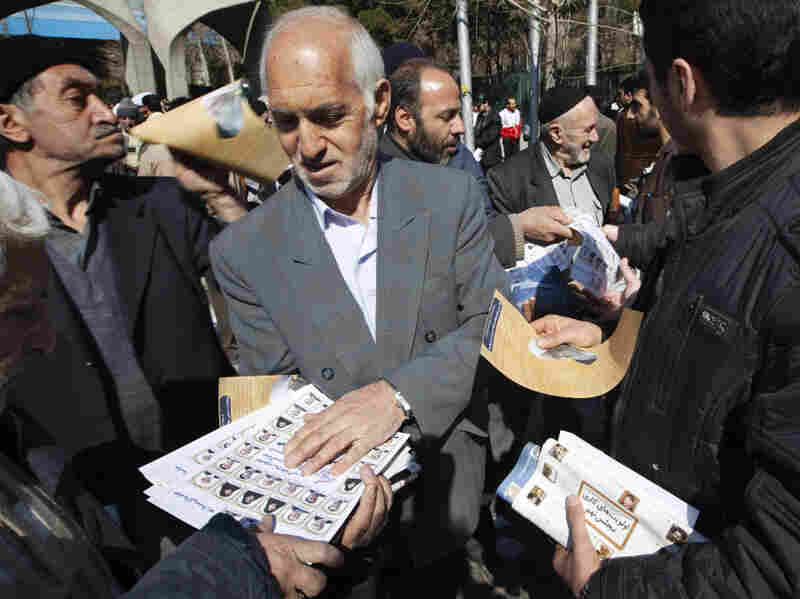 An Iranian man passes out election leaflets after Friday prayers in Tehran last week.