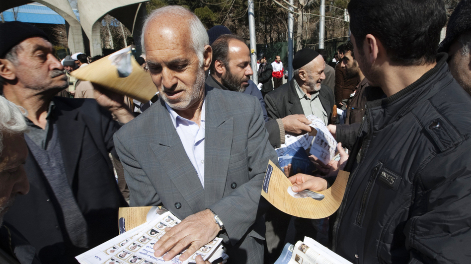 An Iranian man passes out election leaflets after Friday prayers in Tehran last week.  (Reuters/Landov)