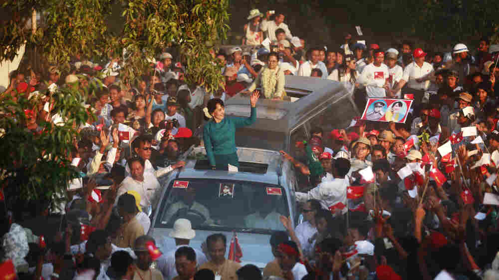 Supporters greet Myanmar's pro-democracy icon Aung San Suu Kyi, atop her vehicle, as she arrives at an election campaign rally in Thongwa village, Myanmar, on Sunday. The country's new government is holding legislative elections on April 1.