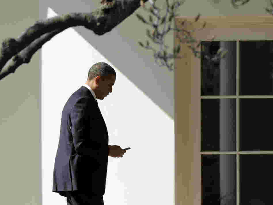 President Obama appears to check smartphone as he heads for the Oval Office after speaking to the UAW, Tuesday, Feb. 28, 2012.