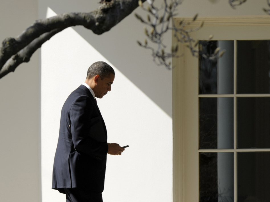 President Obama appears to check smartphone as he heads for the Oval Office after speaking to the UAW, Tuesday, Feb. 28, 2012. (AP)