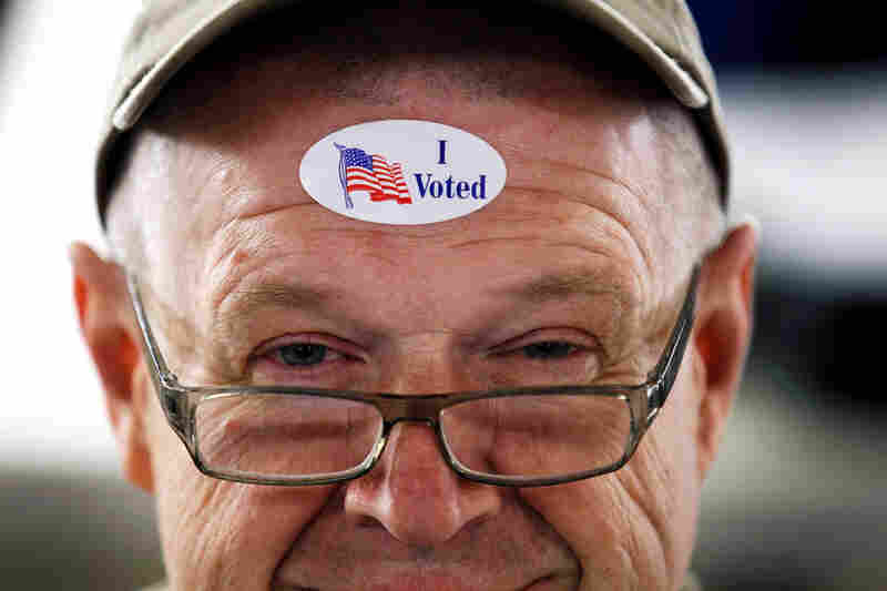 "John Vandermark wears an ""I Voted"" sticker after voting in the Michigan primary at Royal Oak Farmers Market, in Royal Oak."