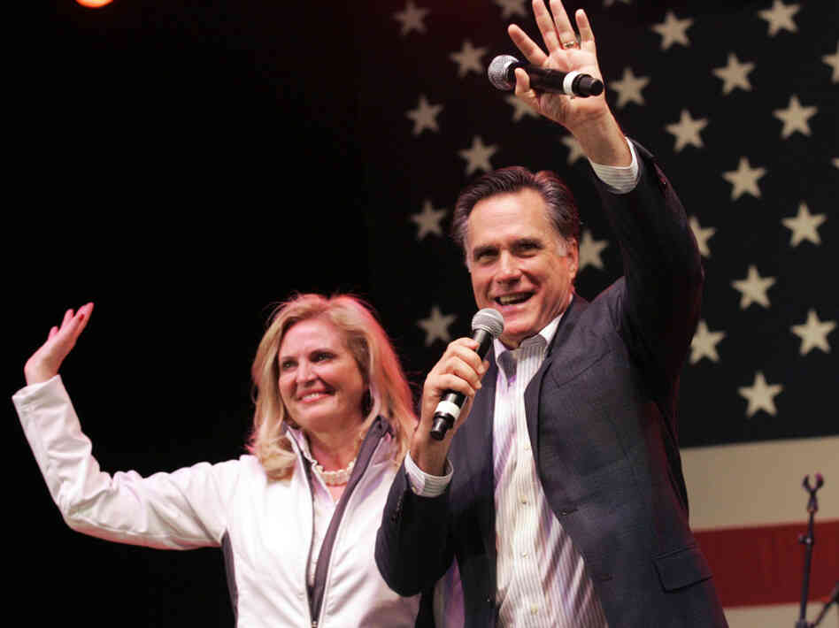 In a final bit of campaigning before Tuesday's vote, Mitt Romney and his wife, Ann, wave to his supporters during a campaign stop in Royal Oak, Mich., on Monday night.