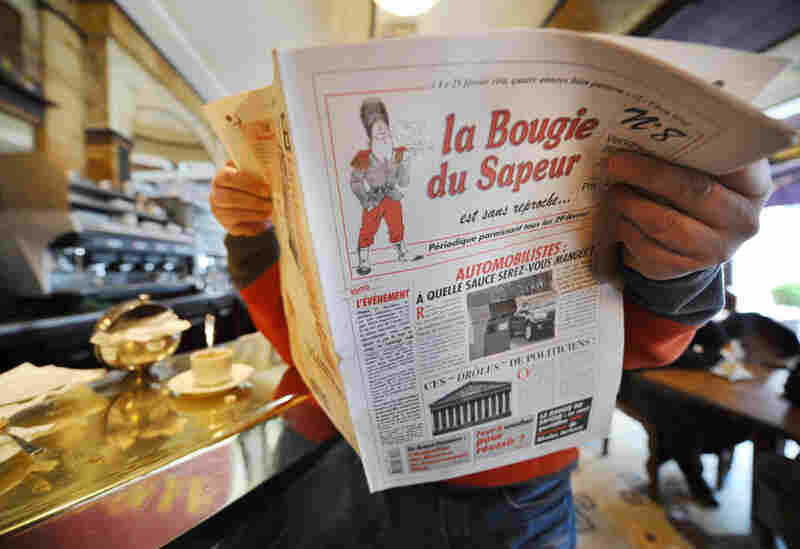 """A man reads a copy of the satirical newspaper La Bougie du Sapeur (The Sapper's Candle), published every leap day, in a Parisian cafe on Feb. 29, 2008. The paper's tagline is """"without reproach."""""""