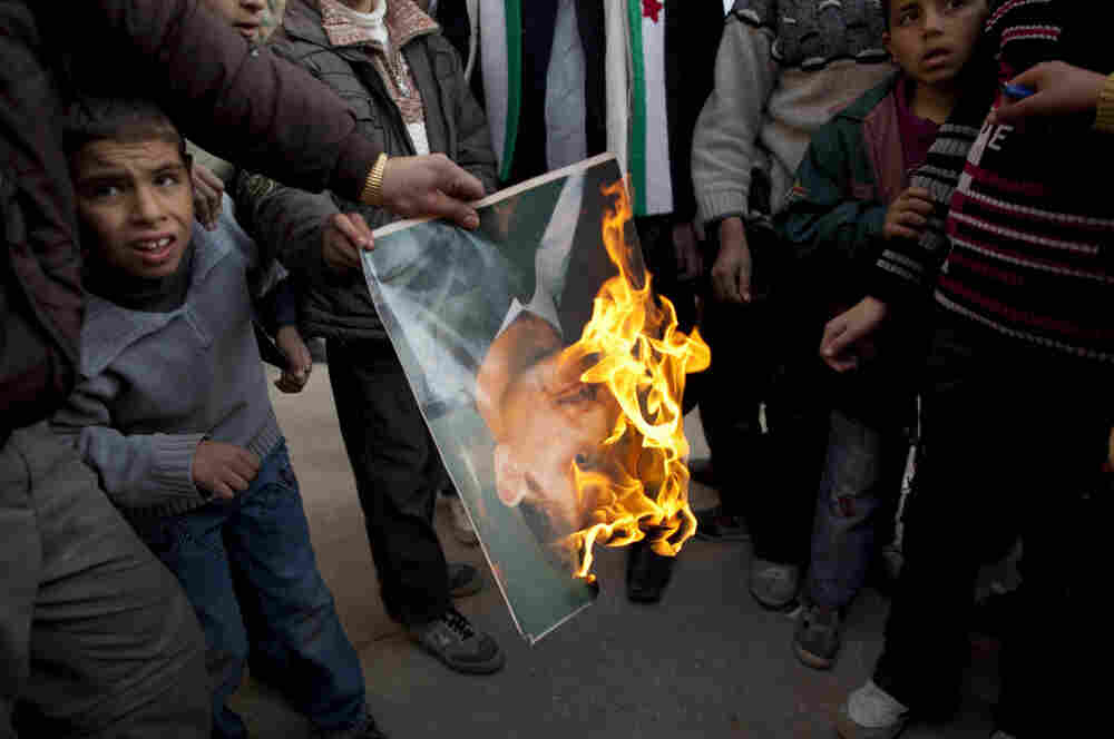 A man burns a portrait of Syrian President Bashar Assad during a demonstration on the outskirts of Idlib, northern Syria, on Sunday.