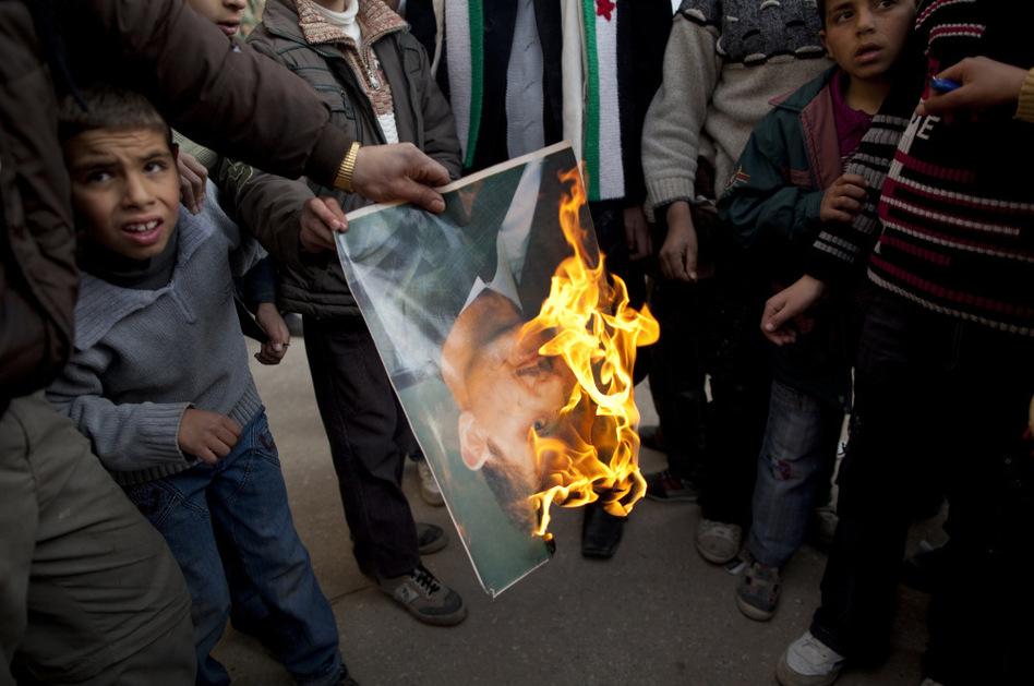 A man burns a portrait of Syrian President Bashar Assad during a demonstration on the outskirts of Idlib, northern Syria, on Sunday.  (Rodrigo Abd/AP)