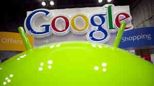 A sign for Google is displayed behind the Google android robot, at the National Retail Federation in New York. Google is planning to roll out a new privacy policy Thursday.
