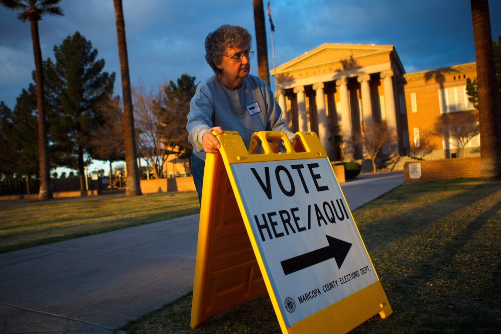 Volunteer Vicki Groff points voters to the polls in Phoenix. Romney won 47.3 percent of the vote in Arizona; Santorum got 26.6.