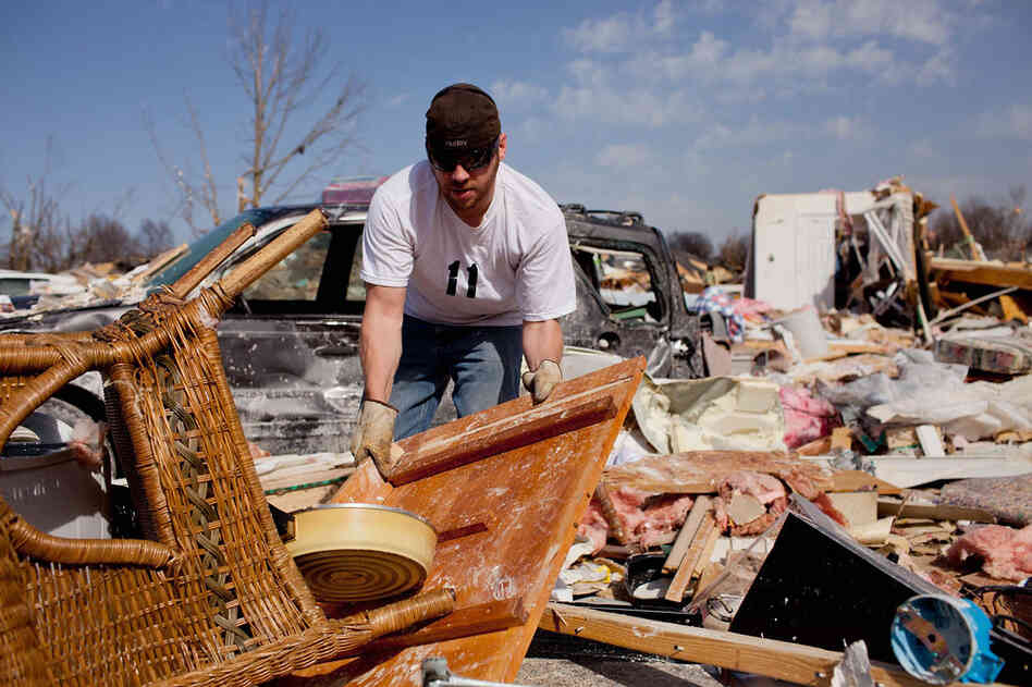 Douglas Osman sorts through debris at his grandmother's house in Harrisburg, Ill. Mary Osman was killed after the tornado hit.