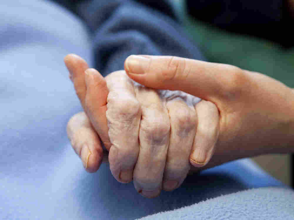 A young hand touches and holds an old wrinkled hand.  In the first hour, author Sandra Tsing Loh talks about the challenges of caring for her aging father.