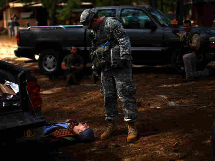 A U.S. Army trainer examines the scene after a mock battle. The man on the ground was playing the role of an Afghan policeman.