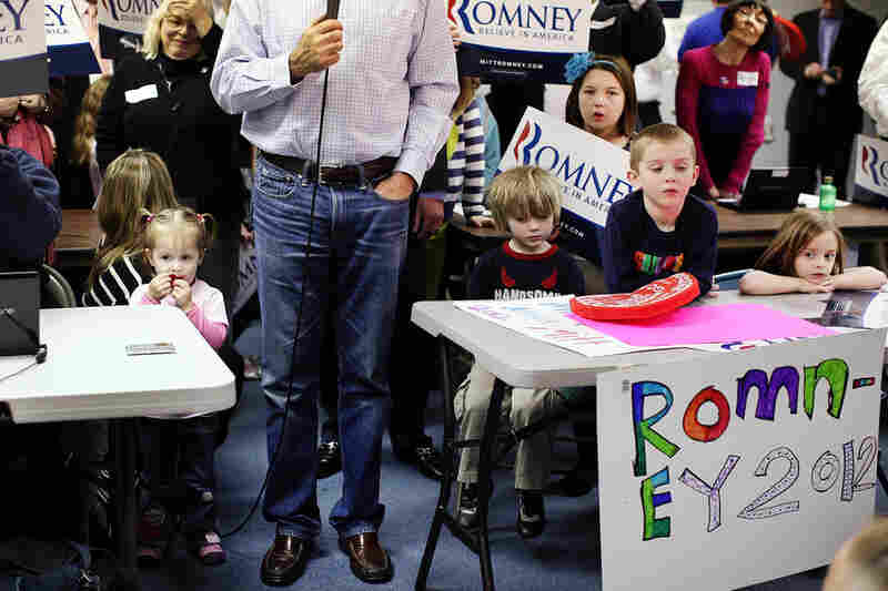 Surrounded by children, Mitt Romney speaks to the media after a visit to his Michigan campaign headquarters in Livonia.